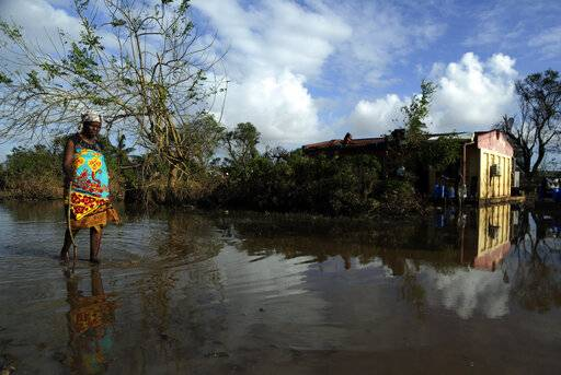 A woman walks along a flooded road in Buzi district, 200km outside Beira, Mozambique, Saturday, March 23, 2019. A second week has begun with efforts to find and help some tens of thousands of people in devastated parts of southern Africa, with some hundreds dead and an unknown number of people still missing.