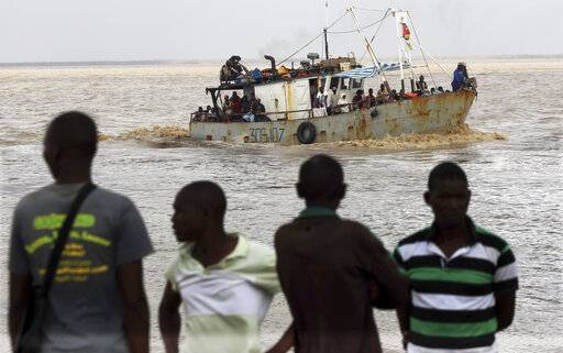 A group of men watch the arrival of a boat carrying displaced families rescued from a flooded area of Buzi district, 200 kilometers (120 miles) outside Beira, Mozambique, on Saturday, March 23, 2019. A second week has begun with efforts to find and help some tens of thousands of people in devastated parts of southern Africa, with some hundreds dead and an unknown number of people still missing.