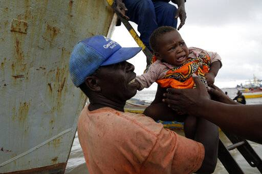 A young girl is carried off the boat after being rescued from a flooded area of Buzi district, 200km outside Beira, Mozambique, Saturday, March 23, 2019. A second week has begun with efforts to find and help some tens of thousands of people in devastated parts of southern Africa, with some hundreds dead and an unknown number of people still missing.