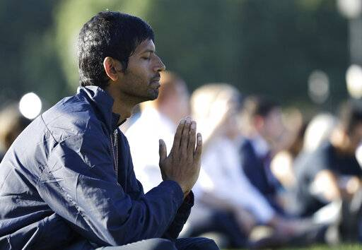 A man prays during a vigil in Hagley Park following the March 15 mass shooting in Christchurch, New Zealand, Sunday, March 24, 2019. (AP Photo/Mark Baker)