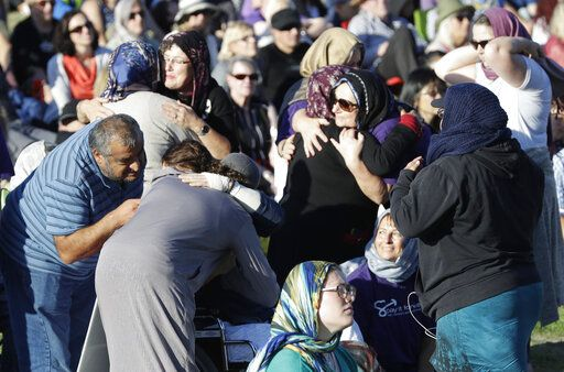 People embrace in a show of love during a vigil in Hagley Park following the March 15 mass shooting in Christchurch, New Zealand, Sunday, March 24, 2019.
