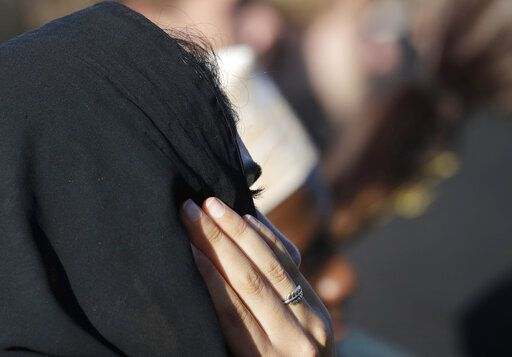 A Muslim woman wears a ring showing a silver fern during a vigil in Hagley Park following the March 15 mass shooting in Christchurch, New Zealand, Sunday, March 24, 2019.