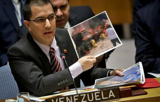 FILE - In this Feb. 26, 2019 file photo, Venezuela Foreign Affairs Minister Jorge Arreaza shows pictures he said represent opposition members initiating violence, during a meeting on Venezuela in the U.N. Security Council at U.N. headquarters. Arreaza has accused the United States of violating articles of the Vienna Convention on Diplomatic Relations that require host countries to protect foreign embassy buildings even when ties are severed.