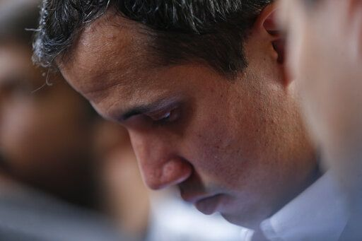 In this March 21, 2019 photo, opposition leader Juan Guaido, who has declared himself interim president of the country, attends an event at a school where he delivered humanitarian aid, in Caracas, Venezuela. Despite the fact that Colombia recognizes Guaido as Venezuela's legitimate president, the ambassador he sent to Bogota does not have access to the consulate or the ability to issue passport extensions.