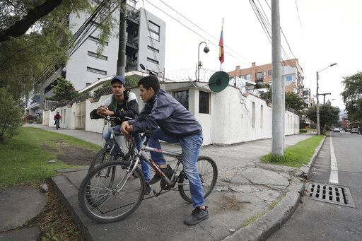 In this March 19, 2019 photo, Venezuelan citizens sit parked on their bikes outside their consulate after learning it was closed, in Bogota, Colombia. Venezuelan leader Nicolas Maduro has severed ties with the neighboring Andean nation where over a million of his compatriots have fled in recent years, recalling all his diplomats and leaving the consulate and embassy buildings closed.