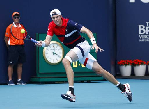 John Isner of USA, returns a volley to Albert Ramos-Vinglas of Spain, during the Miami Open tennis tournament, Sunday, March 24, 2019, in Miami Gardens, Fla.