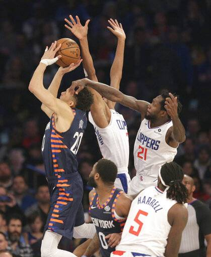 New York Knicks forward Kevin Knox (20), left, drives through Los Angeles Clippers defenders during the first half of an NBA basketball game, Sunday, March 24, 2019, in New York.