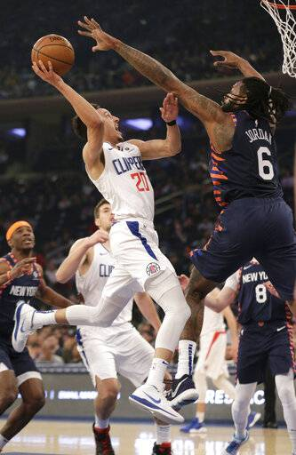 Los Angeles Clippers Landry Shamet, left, is defended by New York Knicks DeAndre Jordan (6) during the first half of an NBA basketball game, Sunday, March 24, 2019, in New York.