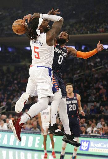 New York Knicks guard Kadeem Allen (0), right, fouls Los Angeles Clippers forward Montrezl Harrell (5) who drives to the basket during the first half of an NBA basketball game, Sunday, March 24, 2019, in New York.