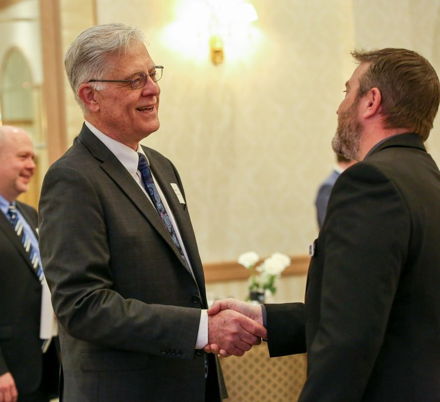 Rolling Meadows Mayor Len Prejna greets Brian Selders, superintendent of communications and IT at the Northwest Special Recreation Association, following the mayor's address to the business community Monday afternoon.