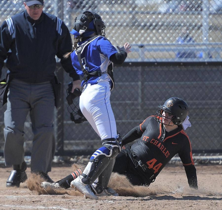 St. Charles East's Alexandra Wooten slides safely into home as Burlington Central catcher Peyton Curtis handles a high throw Monday in St. Charles.