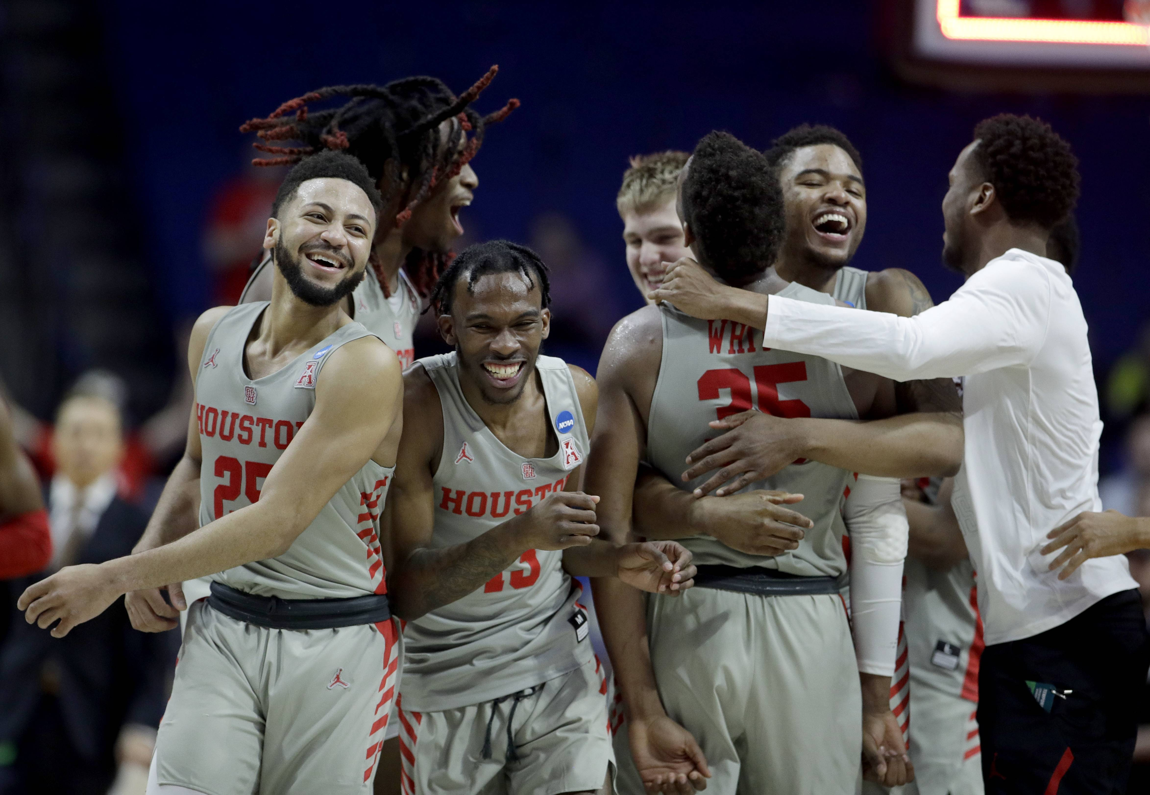 Houston players celebrate Sunday after beating Ohio State in the NCAA Tournament in Tulsa, Oklahoma. Houston won 74-59.