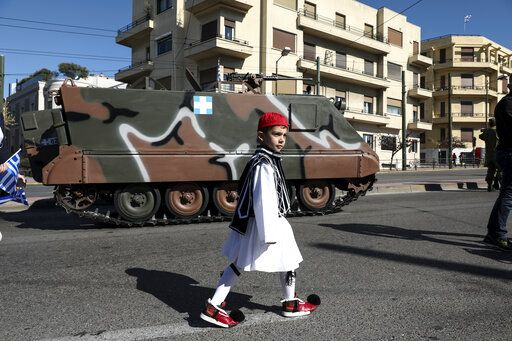 A boy dressed in traditional costume walks in front of a military vehicle ahead of a parade in Athens, on Monday March 25, 2019. The parade commemorates Greek Independence Day, which marks the start of the war of independence in 1821 against the 400-year Ottoman rule.
