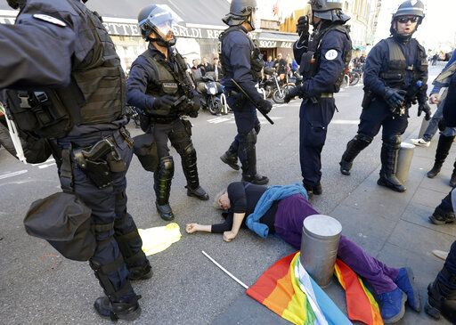 "FILE - In this Saturday, March 23, 2019 file picture, anti-globalization activist Genevieve Legay, 73, lies unconscious after collapsing on the ground during a protest in Nice, southeastern France, as part of the 19th round of the yellow vests movement. Genevieve Legay was waving a rainbow flag marked ""Peace"" and a yellow vest when riot police carrying shields suddenly pushed toward the group of a few dozen protesters Saturday."