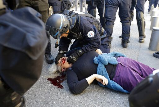 "EDS NOTE: GRAPHIC CONTENT. FILE - In this Saturday, March 23, 2019 file picture, a police officer inspects anti-globalization activist Genevieve Legay, 73, as she lies unconscious after collapsing on the ground during a protest in Nice, southeastern France, as part of the 19th round of the yellow vests movement. Genevieve Legay was waving a rainbow flag marked ""Peace"" and a yellow vest when riot police carrying shields suddenly pushed toward the group of a few dozen protesters Saturday."