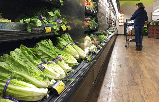 FILE- In this Nov. 20, 2018, file photo Romaine lettuce still sits on the shelves as a shopper walks through the produce area of an Albertsons market in Simi Valley, Calif. Some DNA testing services are offering dietary insights tailored to genetic profiles. The Associated Press tried two services and found that each mostly just reinforced conventional dietary advice.
