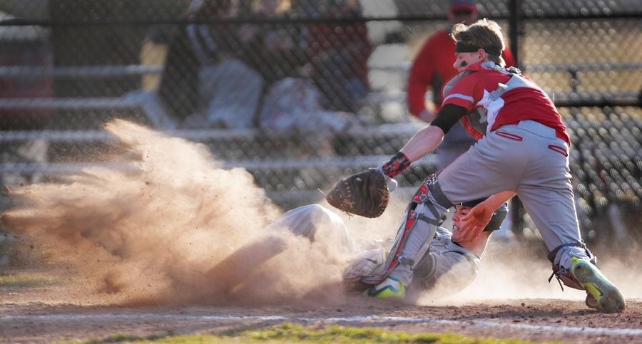 St. Edward's Benjamin Salzmann is tagged out in a cloud of dust by Aurora Christian catcher Josh Smoot to end the fourth inning tied at 7-7 in Aurora Tuesday.