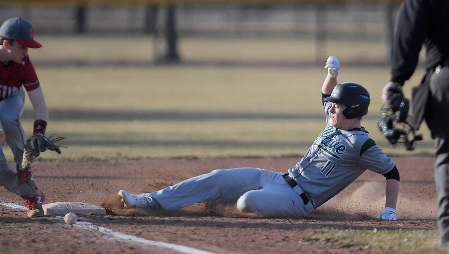 Aurora Christian third baseman Declan Palmquist can't stop a bad bounce on a throw as St. Edward's Benjamin Salzmann slides safely in a baseball game in Aurora Tuesday.