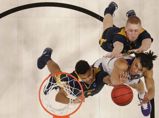 Kansas State guard Mike McGuirl, bottom right, shoots against UC Irvine guard Evan Leonard, left, and UC Irvine forward Collin Welp during the second half of a first round men's college basketball game in the NCAA Tournament Friday, March 22, 2019, in San Jose, Calif.