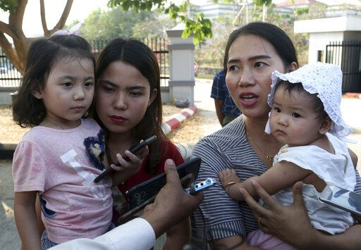 Chit Su Win, wife of Reuters journalist Kyaw Soe Oo, left, and Pan Ei Mon, right, wife of Reuters journalist Wa Lone, hold their children as they leave the Supreme Court after hearing an appeal of the two journalists in Naypyitaw, Myanmar, Tuesday, March 26, 2019. Myanmar's Supreme Court agreed Tuesday to rule on an appeal filed by lawyers for two Reuters journalists sentenced to seven years in prison for their reporting on Myanmar's brutal crackdown on Rohingya Muslims.