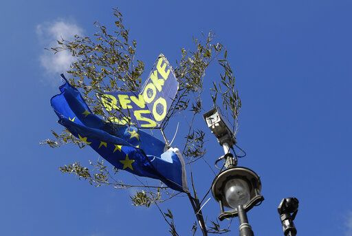 A European Union flag and a banner are caught in a tree alongside a CCTV camera in London, Monday, March 25, 2019. British Prime Minister Theresa May is under intense pressure Monday to win support for her Brexit deal to split from Europe.