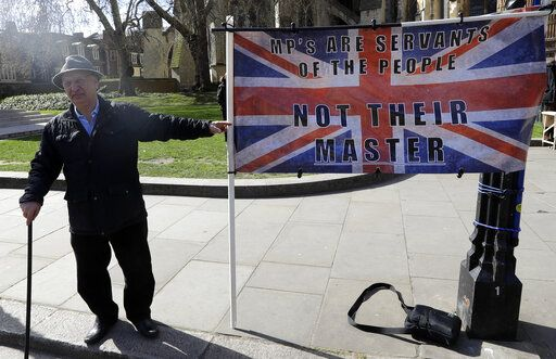 A campaigner holds a banner outside Parliament in London, Monday, March 25, 2019. British Prime Minister Theresa May is under intense pressure Monday to win support for her Brexit deal to split from Europe.