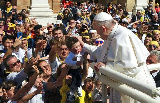 Pope Francis caresses a child as he leaves the Basilica of Our Lady of Loreto where he celebrated mass and prayed in the shrine containing a small house traditionally venerated as the house of Mary, and believed miraculously transplanted from the Holy Land inside the Basilica, in central Italy, during a one-day visit, Monday, March 25, 2019. The pope chose Loreto to sign the Post-Synodal Exhortation of last October's Synod of Bishops.