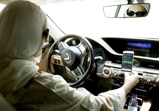 In this June 24, 2018 photo, Ammal Farahat, who has signed up to be a driver for Careem, a regional ride-hailing service that is a competitor to Uber, opens the Careem app on her mobile phone before she starts driving, in Riyadh, Saudi Arabia. Ride-hailing service Uber announced on Tuesday, March 26, 2019 it has acquired Mideast competitor Careem for $3.1 billion, giving the San Francisco-based firm the commanding edge in a region with a large young, tech-savvy population.
