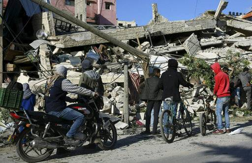 Residents inspect the damage of a destroyed multi-story building of Hamas-affiliated insurance company, in Gaza City, Tuesday, March 26, 2019. A tense quiet took hold Tuesday morning after a night of heavy fire as Israeli aircraft bombed targets across the Gaza Strip and Gaza militants fired rockets into Israel in what threatened to devolve into a major conflict two weeks before the Israeli election.