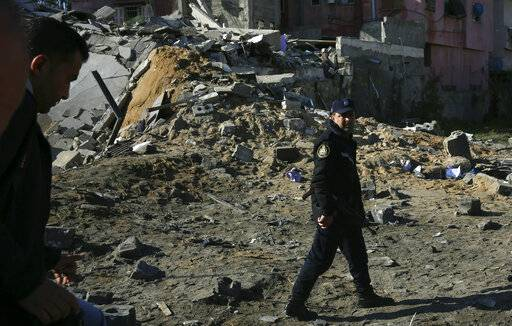 A Hamas police officer inspects the damage of the destroyed multi-story building of Hamas-affiliated insurance company, in Gaza City, Tuesday, March 26, 2019. A tense quiet took hold Tuesday morning after a night of heavy fire as Israeli aircraft bombed targets across the Gaza Strip and Gaza militants fired rockets into Israel in what threatened to devolve into a major conflict two weeks before the Israeli election.