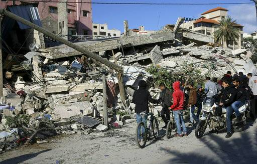 Residents inspect the damage of the destroyed multi-story building of Hamas-affiliated insurance company, in Gaza City, Tuesday, March 26, 2019. A tense quiet took hold Tuesday morning after a night of heavy fire as Israeli aircraft bombed targets across the Gaza Strip and Gaza militants fired rockets into Israel in what threatened to devolve into a major conflict two weeks before the Israeli election.