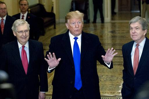 President Donald Trump accompanied by Senate Majority Leader Mitch McConnell of Ky., left, and Sen. Roy Blunt, R-Mo., right, arrives for a Senate Republican policy lunch on Capitol Hill in Washington, Tuesday, March 26, 2019. (AP Photo/Jose Luis Magana)