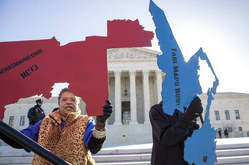 Activists at the Supreme Court opposed to partisan gerrymandering hold up representations of congressional districts from North Carolina, left, and Maryland, right, as justices hear arguments about the practice of political parties manipulating the boundary of a congressional district to unfairly benefit one party over another, in Washington, Tuesday, March 26, 2019. Democrats and Republicans eagerly await the outcome of cases from Maryland and North Carolina because a new round of redistricting will follow the 2020 census, and the decision could help shape the makeup of Congress and state legislatures over the next decade.