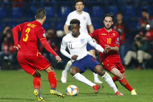 In his debut match for England, Callum Hudson-Odoi, center, vies for the ball with Montenegro's Aleksandar Boljevic, left, and Montenegro's Marko Jankovic, right, during the Euro 2020 group A qualifying soccer match between Montenegro and England at the City Stadium in Podgorica, Montenegro, Monday, March 25, 2019.