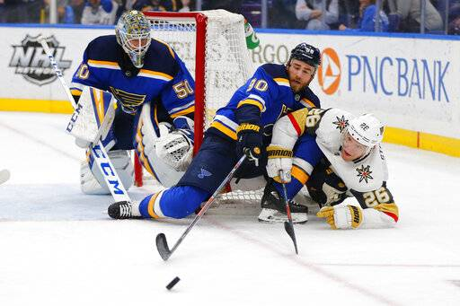St. Louis Blues' goalie Jordan Binnington (50) and Ryan O'Reilly (90) defend the goal against Vegas Golden Knights' Paul Stastny (26) during the third period of an NHL hockey game Monday, March 25, 2019, in St. Louis.