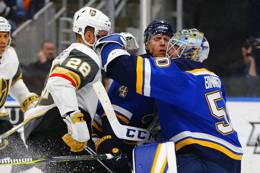 St. Louis Blues' goalie Jordan Binnington (50) makes a save against Vegas Golden Knights' William Carrier (28) as Blues' Carl Gunnarsson (4) defends during the third period of an NHL hockey game Monday, March 25, 2019, in St. Louis.