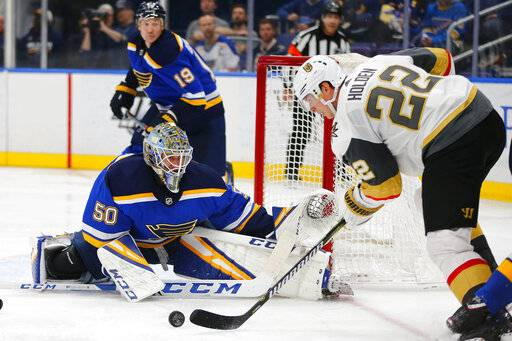 St. Louis Blues' goalie Jordan Binnington (50) looks to make a save against Vegas Golden Knights' Nick Holden (22) during the third period of an NHL hockey game Monday, March 25, 2019, in St. Louis.