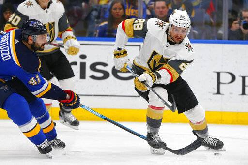 Vegas Golden Knights' William Carrier (28) loses control of the puck against St. Louis Blues' Robert Bortuzzo (41) during the third period of an NHL hockey game Monday, March 25, 2019, in St. Louis.