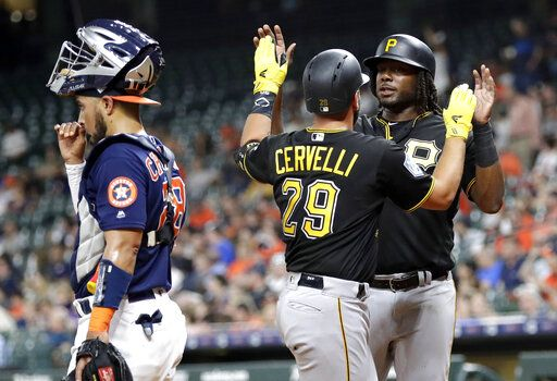 Pittsburgh Pirates' Francisco Cervelli (29) celebrates with Josh Bell, right, after they scored on Cervelli's home run as Houston Astros catcher Robinson Chirinos, left, looks toward the field during the first inning of an exhibition baseball game Monday, March 25, 2019, in Houston.