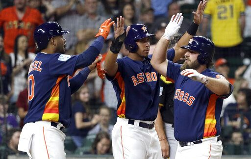 Houston Astros' Tyler White, right, celebrates with Michael Brantley, center, and Yuli Gurriel, left, after they scored on White's home run against the Pittsburgh Pirates during the third inning of an exhibition baseball game Monday, March 25, 2019, in Houston.