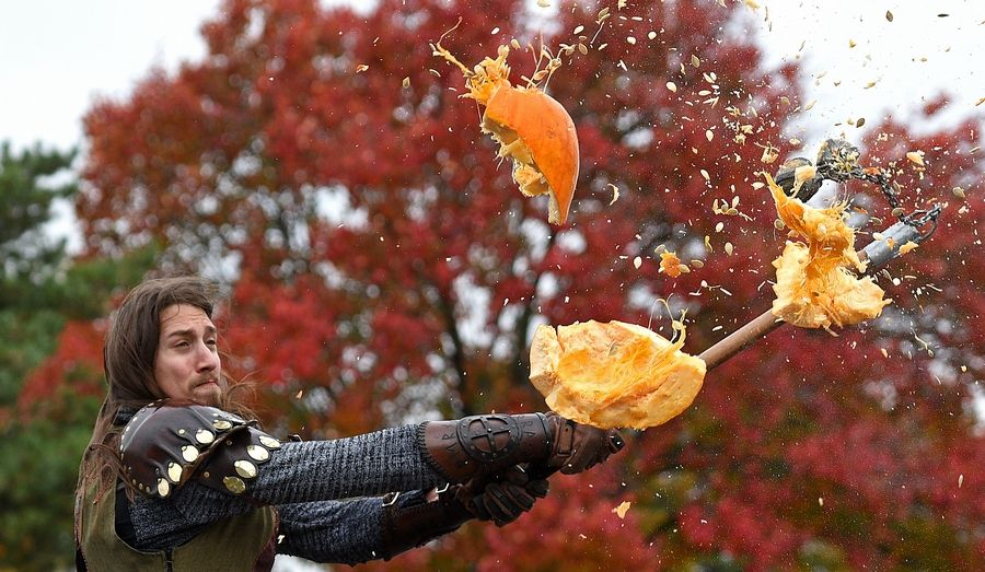 Edward Maciejczyk of Palatine uses a bola to destroy a tossed pumpkin as he and other knights at Medieval Times in Schaumburg in using their weapons to destroy leftover Halloween pumpkins and jack-o-lanterns. This photograph was one of Rick West's several first-place winners in the Best of the Press contest sponsored by the Illinois Press Association.