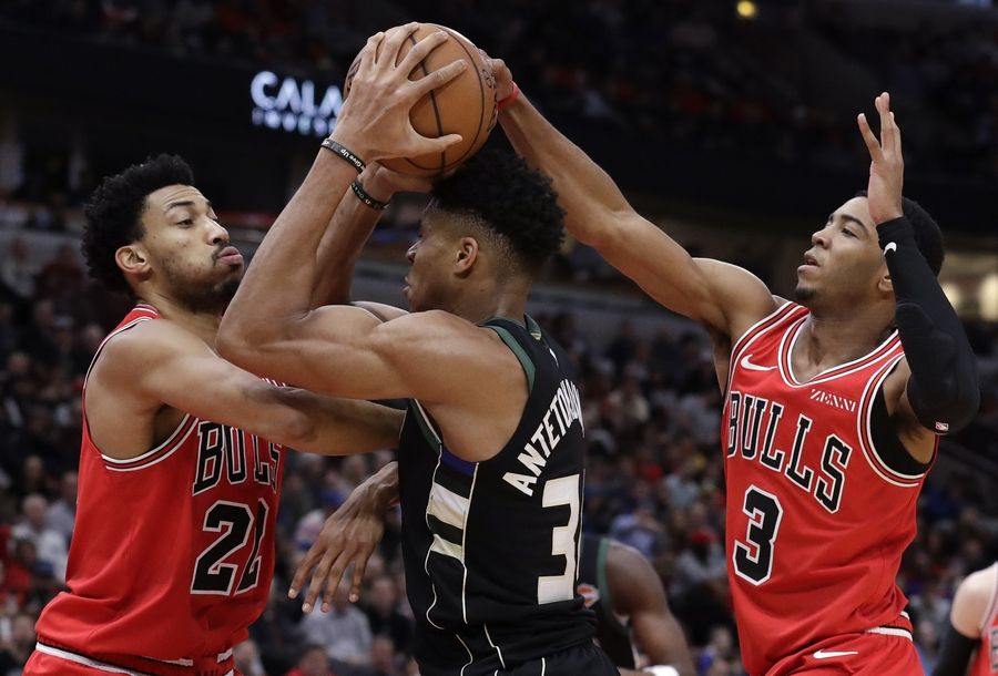 Chicago Bulls forward Otto Porter Jr., left, and guard Shaquille Harrison, right, guard Milwaukee Bucks forward Giannis Antetokounmpo during the second half of an NBA basketball game Monday, Feb. 11, 2019, in Chicago. The Bucks won 112-99.