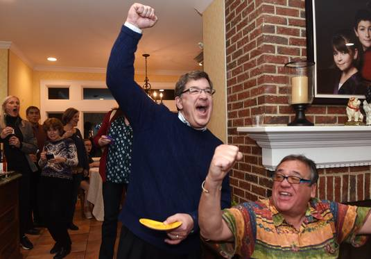 Wheaton mayoral candidate Philip Suess, left, celebrates after being told by supporter Jim Dorf of Wheaton that he had a nearly 300-vote lead with 99 percent of the vote in while watching election results at his home Tuesday.