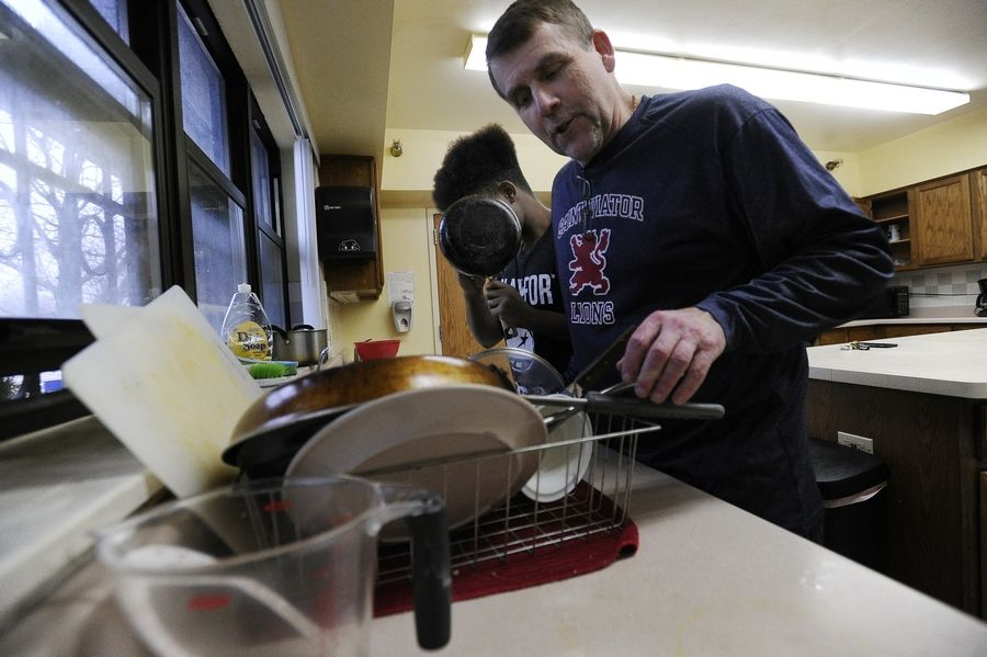 An asylum-seeker from East Africa washes dishes with the Rev. Corey Brost, co-director at Viator House of Hospitality, a suburban home for young immigrants while they wait for their asylum requests to be adjudicated.