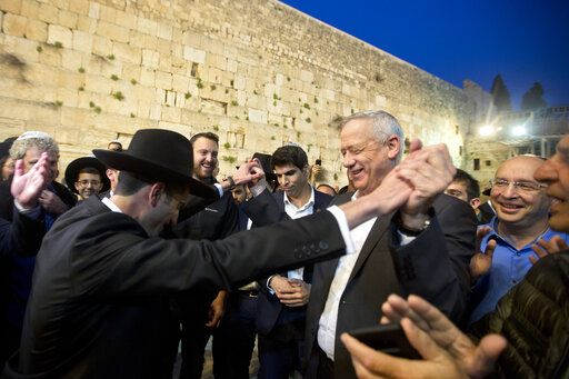 "FILE - In this Thursday, March 28, 2019 file photo, leader of the Blue and White party, former Israeli army chief of staff, Benny Gantz dances with ultra Orthodox Jewish men at the Western Wall, in Jerusalem's Old City. The conflict with the Palestinians has been a central issue in Israeli elections going back decades, but in the campaign ahead of next week's vote it's been notably absent. Prime Minister Netanyahu's main challenger, Gantz, has given Israel's ""peace camp"" some dim hope. His party's platform devotes just a few sentences to the Palestinians, promising ""an open horizon for political settlement"" and pledging to work with Arab neighbors to find a way to ""deepen the separation."""