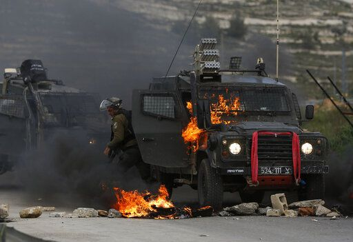 "FILE - In this Wednesday, March 27, 2019 file photo, Israeli border policemen move away from a burning vehicle during clashes with Palestinians at checkpoint Bet El near the West Bank city of Ramallah. The conflict with the Palestinians has been a central issue in Israeli elections going back decades, but in the campaign ahead of next week's vote it's been notably absent. Prime Minister Benjamin Netanyahu's ruling Likud Party has offered no plan for what many believe is the country's most existential problem. His main challenger speaks vaguely of ""separation,"" while Netanyahu's hard-line partners speak openly of the once unthinkable idea of annexing all or parts of the West Bank."