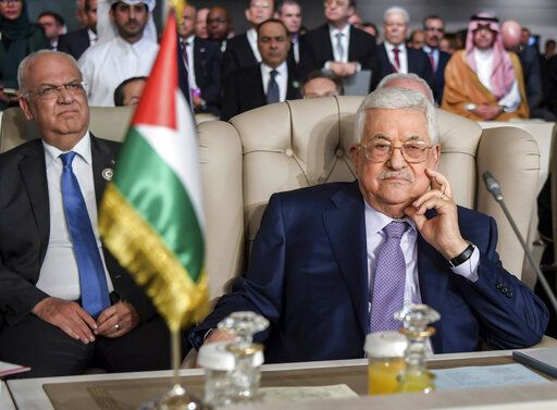 FILE - In this Sunday, March 31, 2019 file photo, Palestinian President Mahmoud Abbas, right, and secretary general of the Palestinian Liberation Organization, Saeb Erekat, attend the the 30th Arab Summit in Tunis, Tunisia. The conflict with the Palestinians has been a central issue in Israeli elections going back decades, but in the campaign ahead of next week's vote it's been notably absent. Prime Minister Benjamin Netanyahu has largely succeeded in his aim of sidelining the Palestinians, thanks in part to widespread pessimism following years of failed peace efforts. (Fethi Belaid/ Pool photo via AP, FIle)