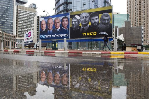 "FILE - In this Saturday, March 16, 2019 file photo, an Ultra-Orthodox Jewish man looks at an elections billboards of the Blue and White party leaders, from left to right, Moshe Yaalon, Benny Gantz, Yair Lapid and Gabi Ashkenazi, alongside a panel on the right showing Prime Minister Benjamin Netanyahu flanked by extreme right politicians, from the left, Itamar Ben Gvir, Bezalel Smotrich and Michael Ben Ari in Ramat Gan, Israel, In a charged campaign that has been heavy on insults and short on substance, Israel's conflict with the Palestinians has been notably absent from the discourse. Hebrew reads on the left billboard ""The nation of Israel lives"" and on the right billboard ""Kahana Lives"" in a reference to a banned ultranationalist party."
