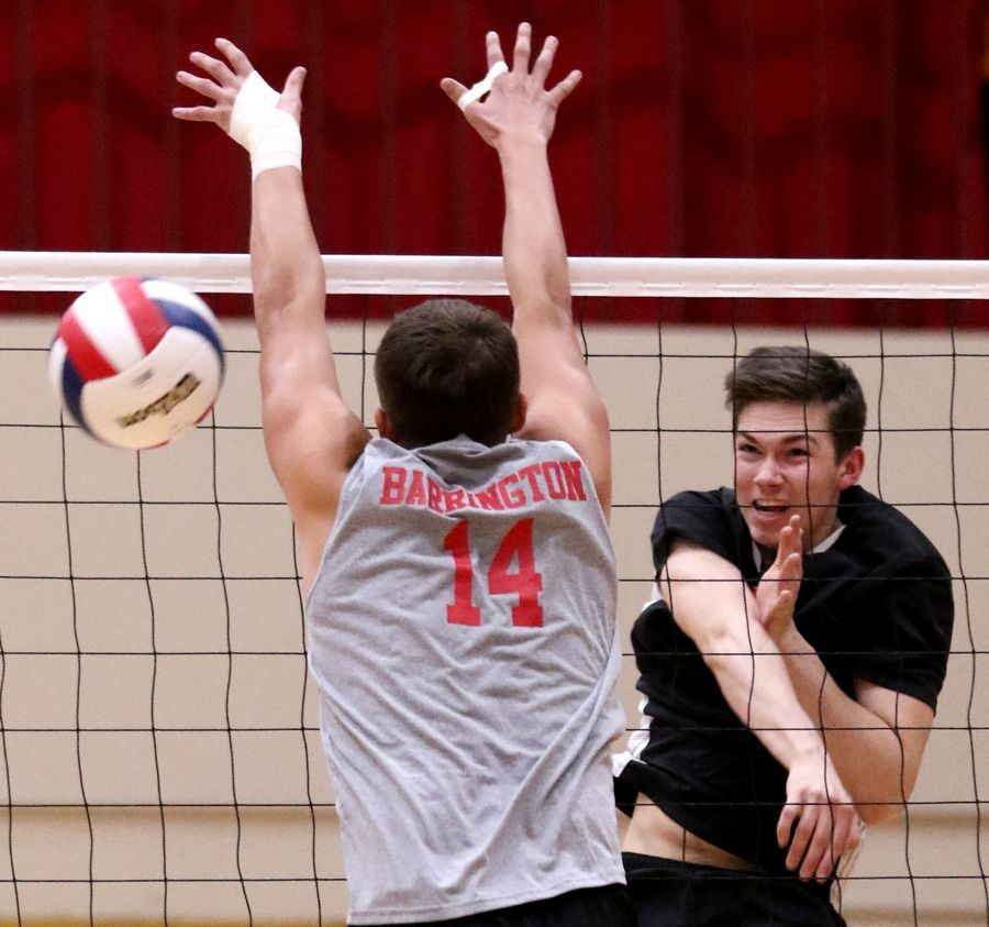Schaumburg's Ryan Regier, right, slams the ball past Barrington's Luke Kolder during varsity boys volleyball in Schaumburg on Thursday.