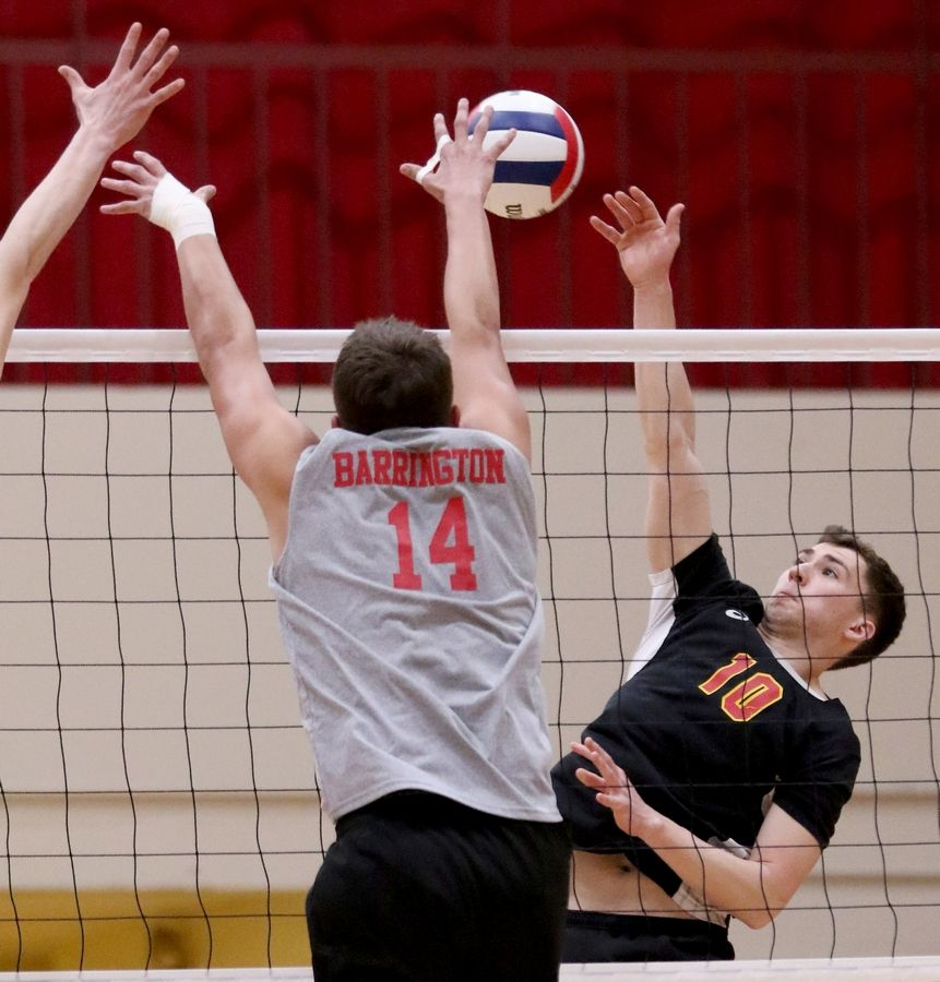 Schaumburg's Michael Knipp, right, hits the ball against Barrington during varsity boys volleyball in Schaumburg on Thursday.